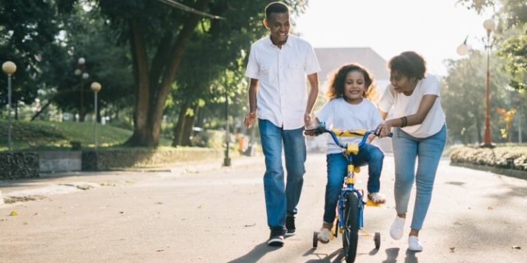 An image of parents teach their kid to ride bicycle.